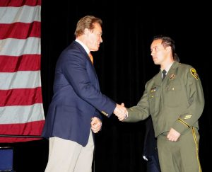 Governor shakes hands with correctional officer for Medal of Valor.