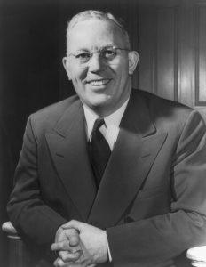Earl Warren smiles in a portrait photograph.