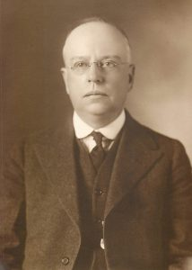 Man in jacket and tie poses for portrait.