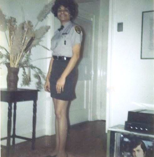 Woman wearing correctional officer uniform, while standing in her living room.