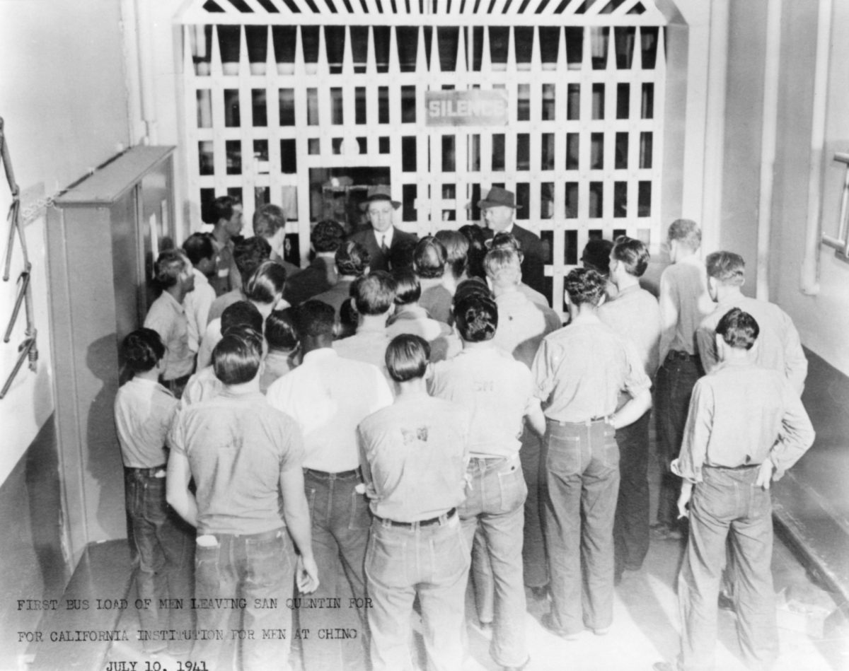 Inmates stand at San Quentin prison gate, waiting to be transported to a new prison.