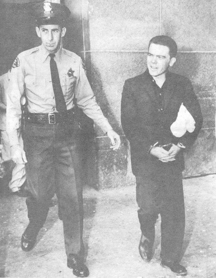 Police officer escorts Bobby Driscoll out of a court house.