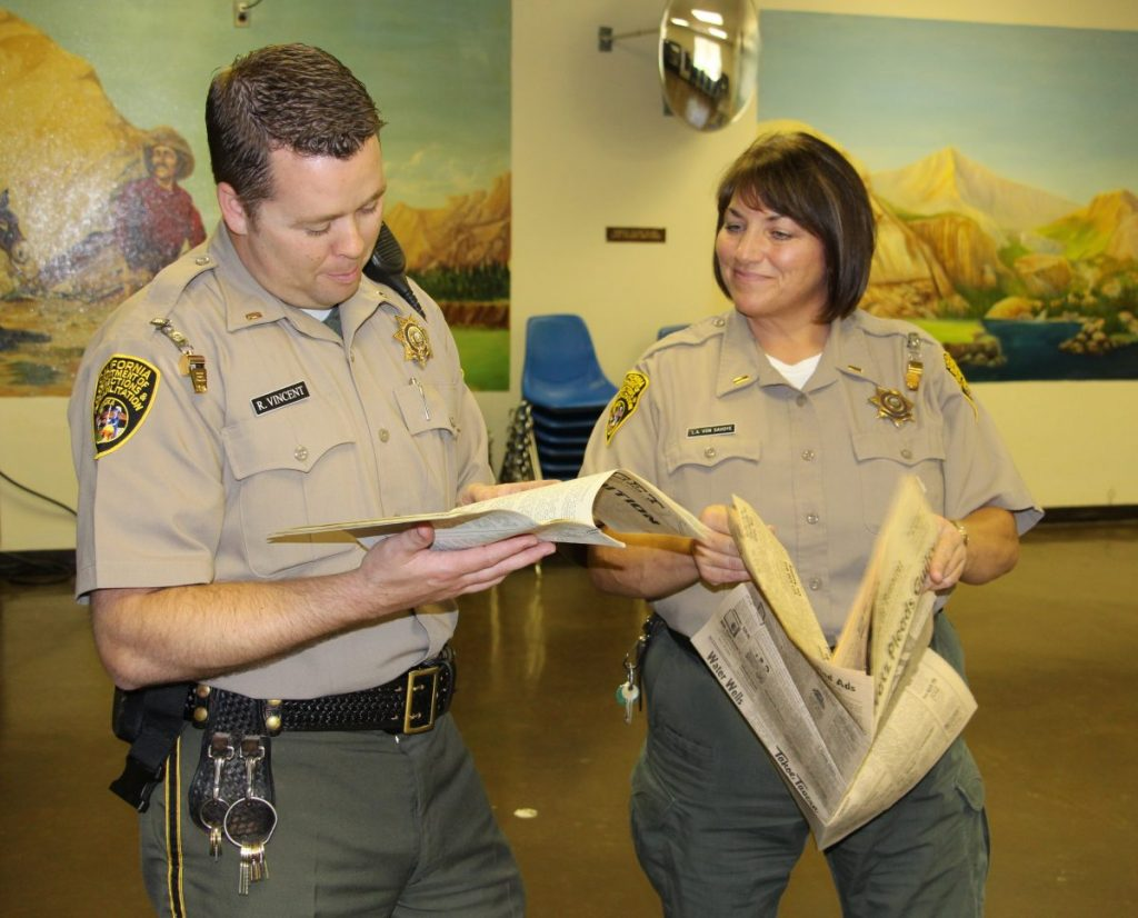 Two correctional lieutenants look at documents pulled from a time capsule.