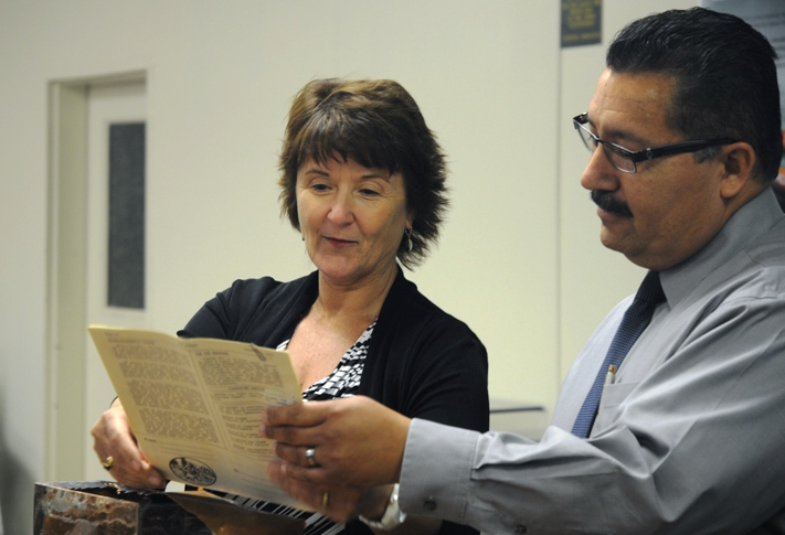 Two people hold a document pulled from a time capsule.