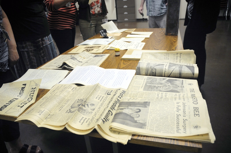 Documents from a time capsule are displayed on a table.