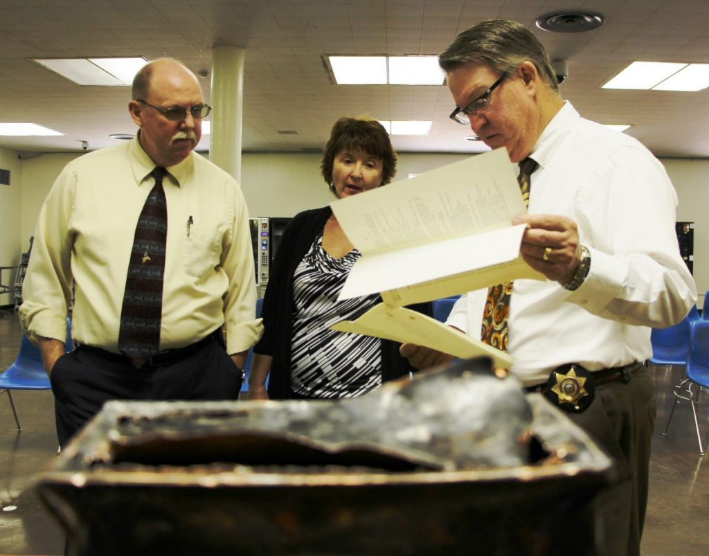Three people stand around an open metal box time capsule.