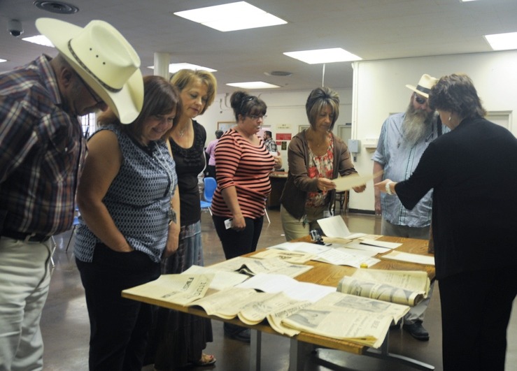 Men and women gather around a table covered with papers from the time capsule.