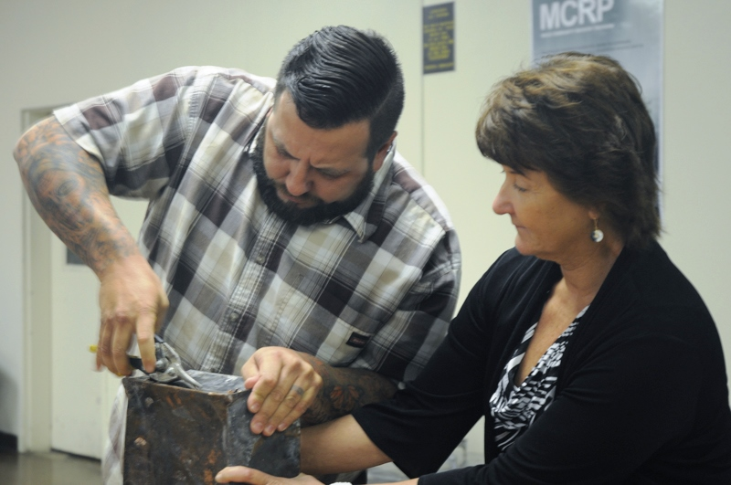 Man uses cutters to get into metal time capsule while a woman holds the box.