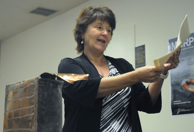 Warden reads a paper found in the time capsule.