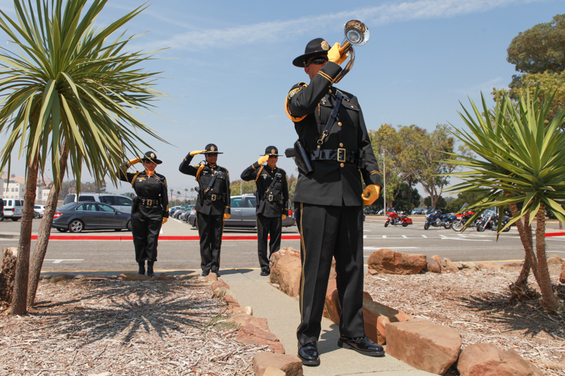 Man in uniform plays bugle while three officers salute.
