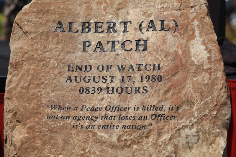 """Writing on stone says Albert (Al) Patch, End of Watch, Aug. 17, 1980, 0839 hours. """"When a Police Officer is killed, it is not an agency that loses an officer, it's an entire nation."""""""