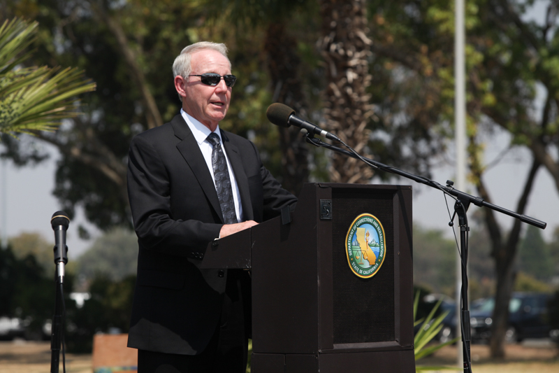 Man in dark suit and sunglasses speaks into microphone.