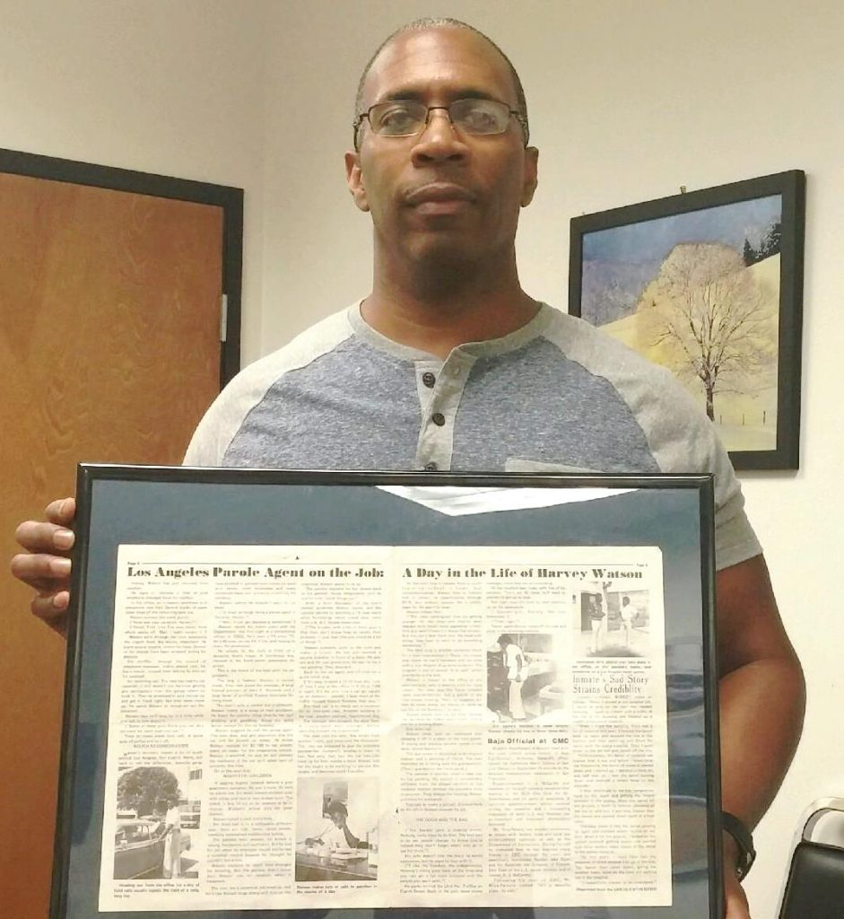 Man holds a framed news article.