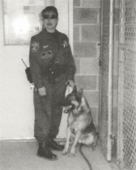 Woman correctional officer holds a dog's leash outside a prison fence.
