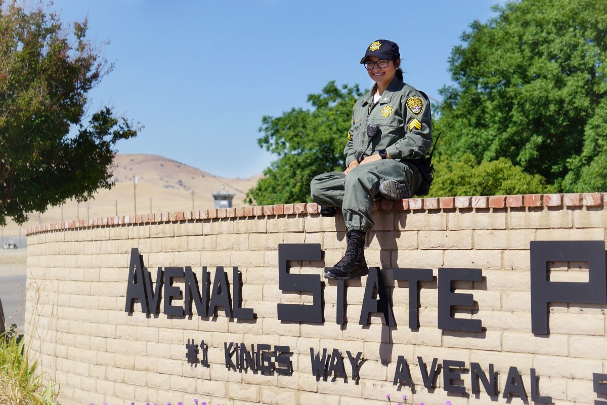 Woman in correctional uniform sits on a wall that says Avenal State Prison.