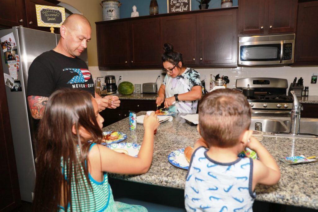 Two children and their parents prepare food in a kitchen.