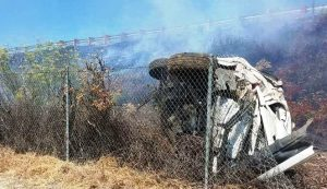 Smoldering hillside with a smashed car on its side.