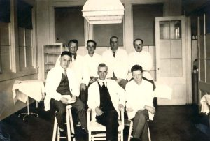 Seven men in lab coats pose for a photo in a prison doctor's office.
