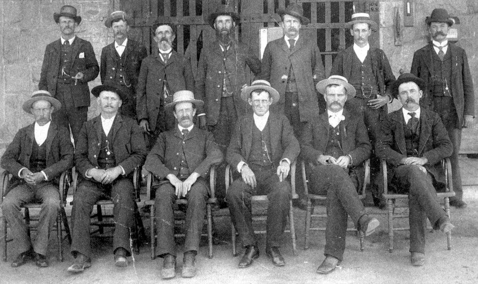 Men in hats, jackets and ties sit or stand in front of a prison gate.