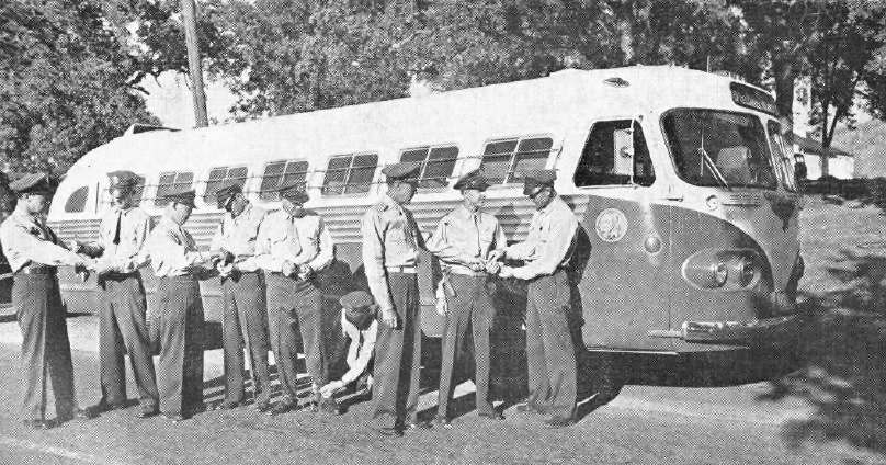 Correctional officers stand in front of a bus.