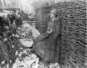 Woman in army helmet stands in trench.