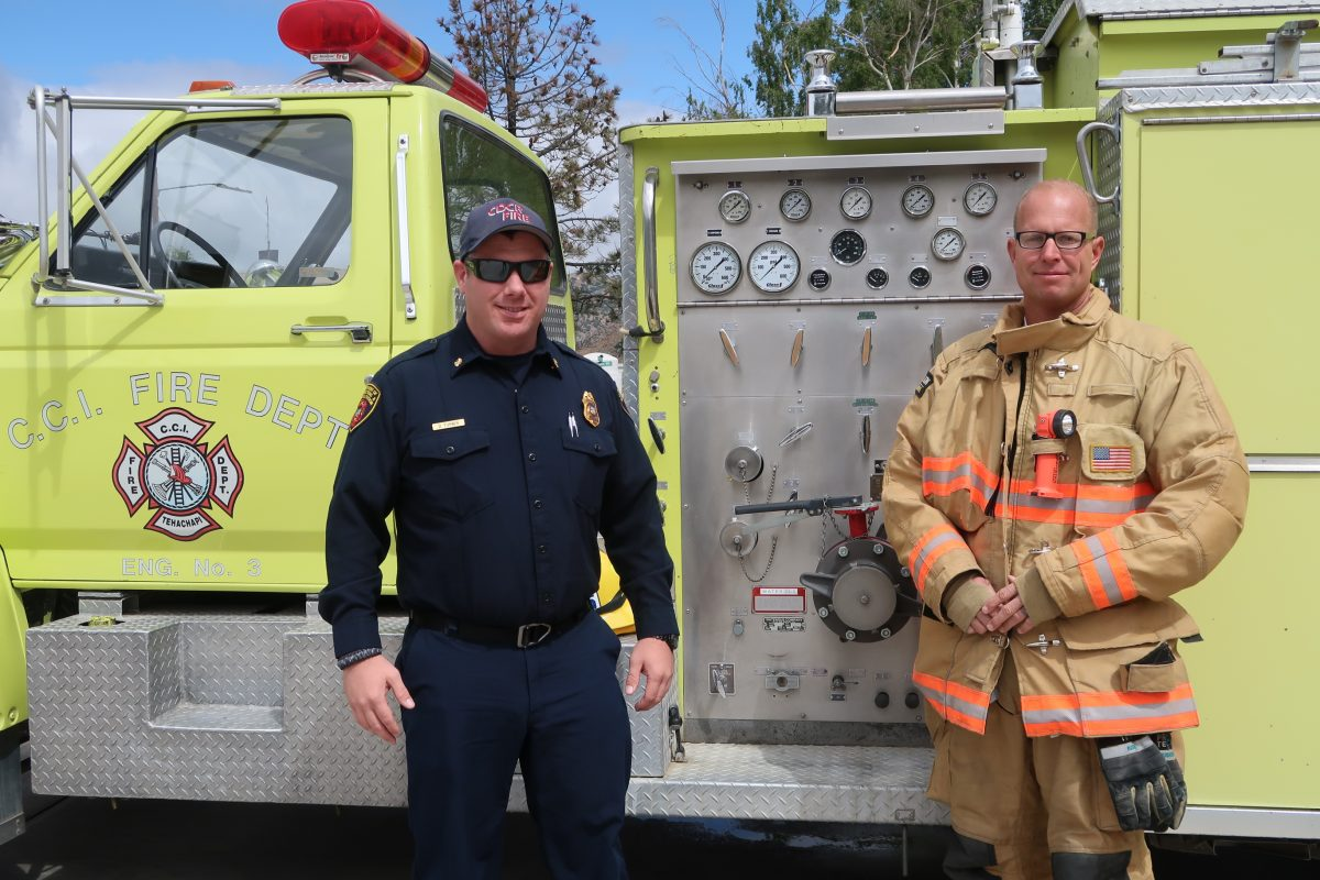 Two men pose in uniform in front of a fire engine.