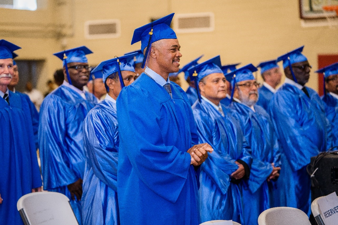 Standing men wear blue caps and gowns.