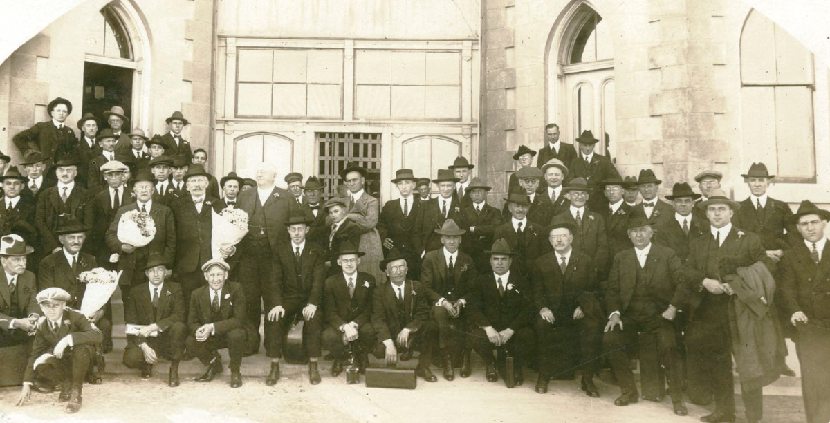 Men in suits stand in front of brick walls.