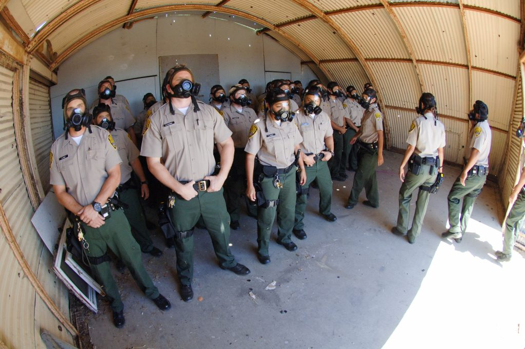 Men and women in uniform wear gas masks.