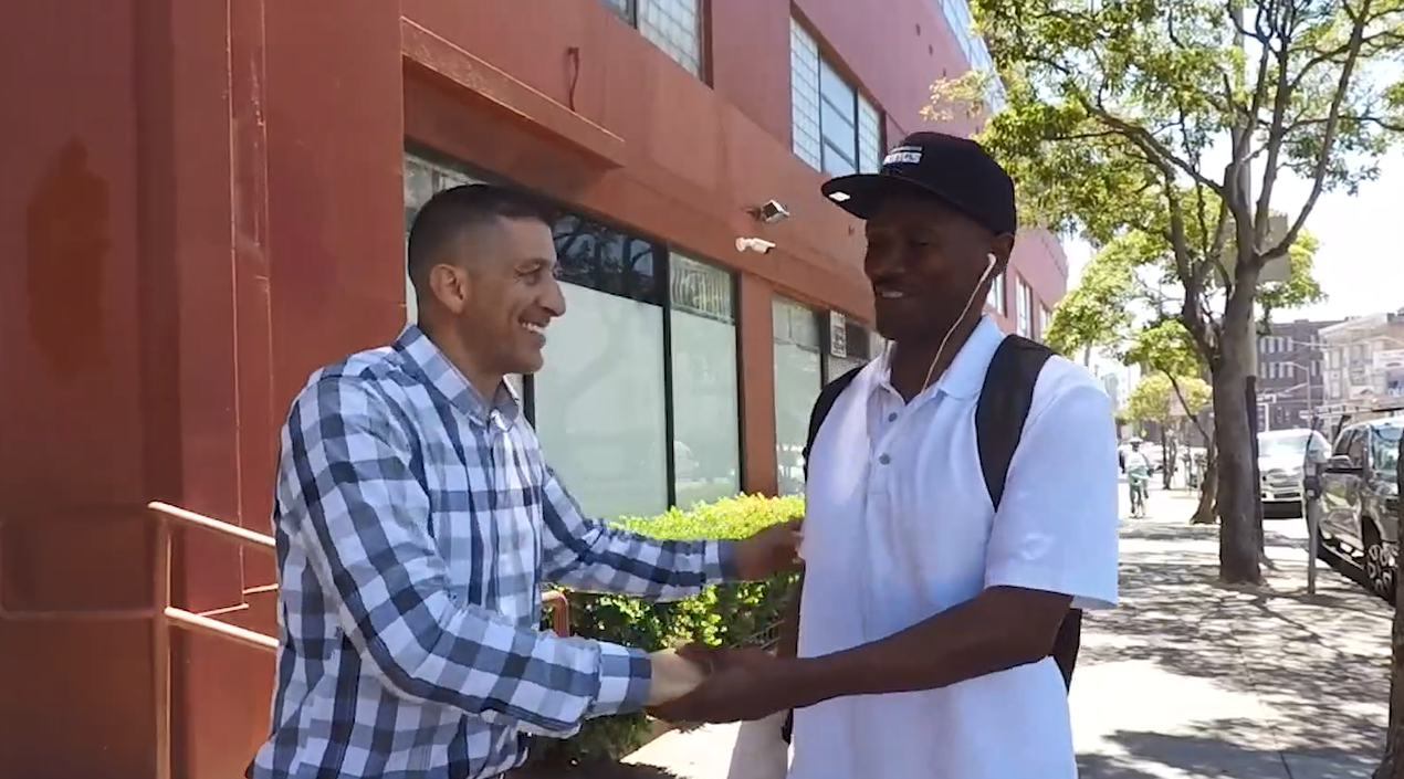 Two men smile and shake hands.