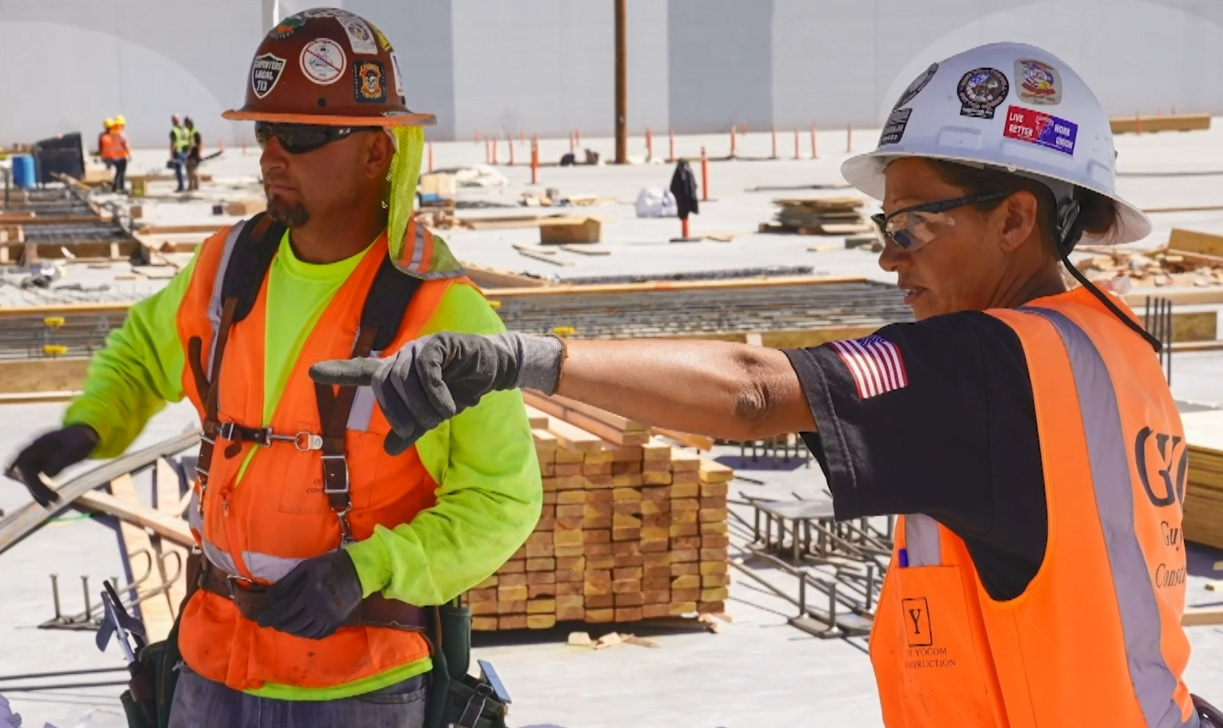 Two people in hardhats work on a site.