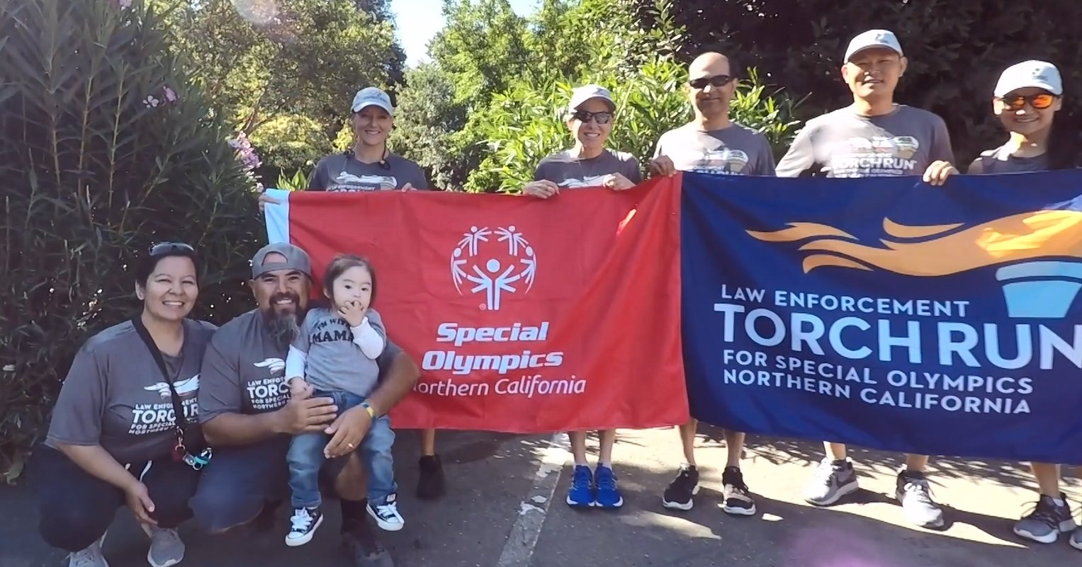 """People hold banners with the words """"Special Olympics"""" and """"Law Enforcement Torch Run."""""""