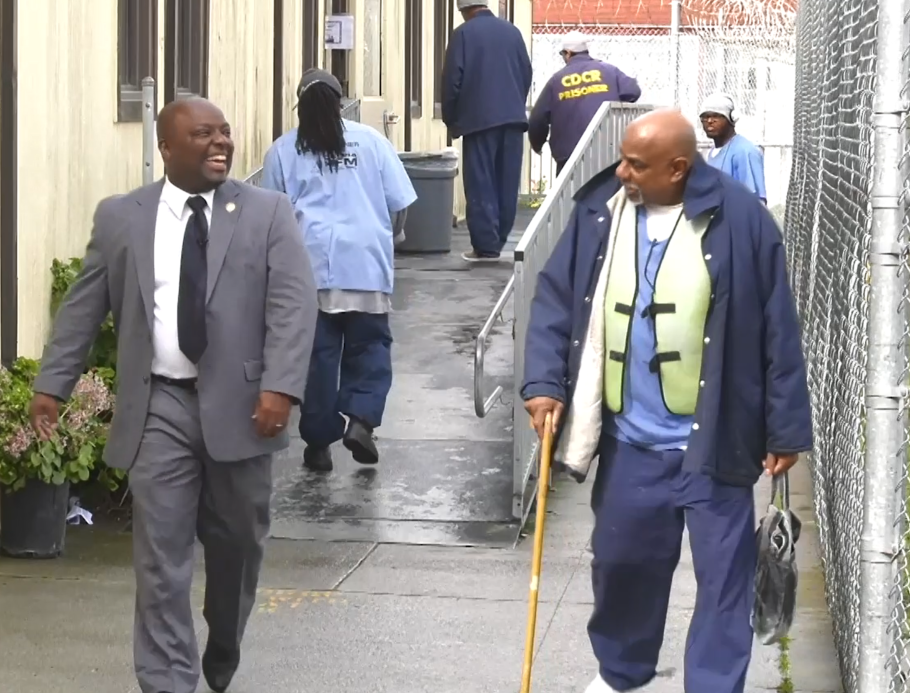 Smiling man in tie and jacket walks by another man with a cane.