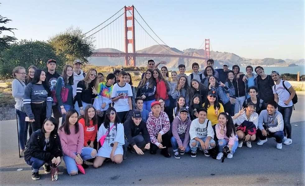 Teenagers stand in front of Golden Gate Bridge.