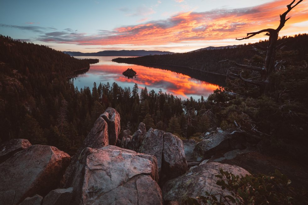Clouds catch orange sunrise that is reflected in lake surrounded by pine trees.