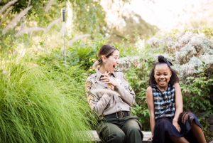 Big Sister volunteer Sergeant Melendez wears uniform laughs with smiling little girl.