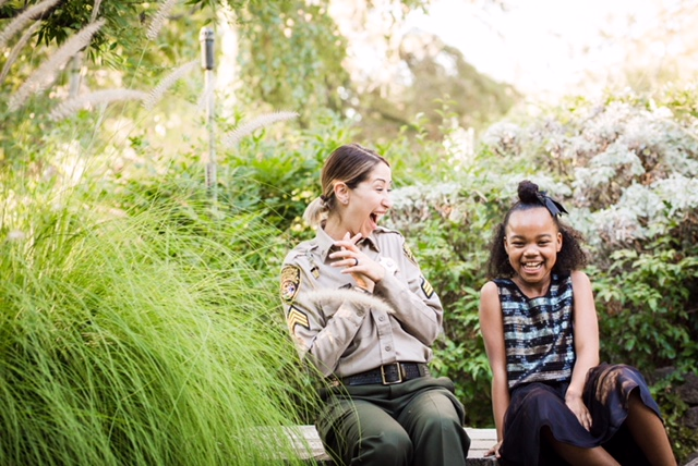 Woman wearing uniform laughs with smiling little girl.