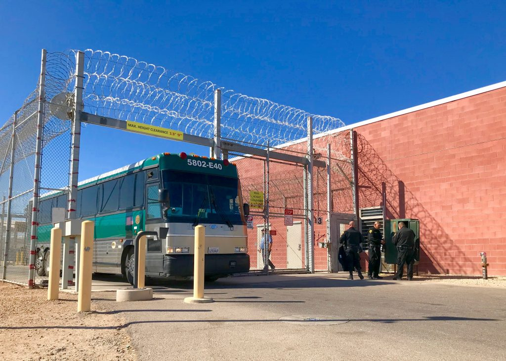 Bus driving through gate as several correctional officers watch.
