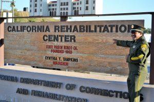 "Man in uniform in front of ""California Rehabilitation Center"" sign."