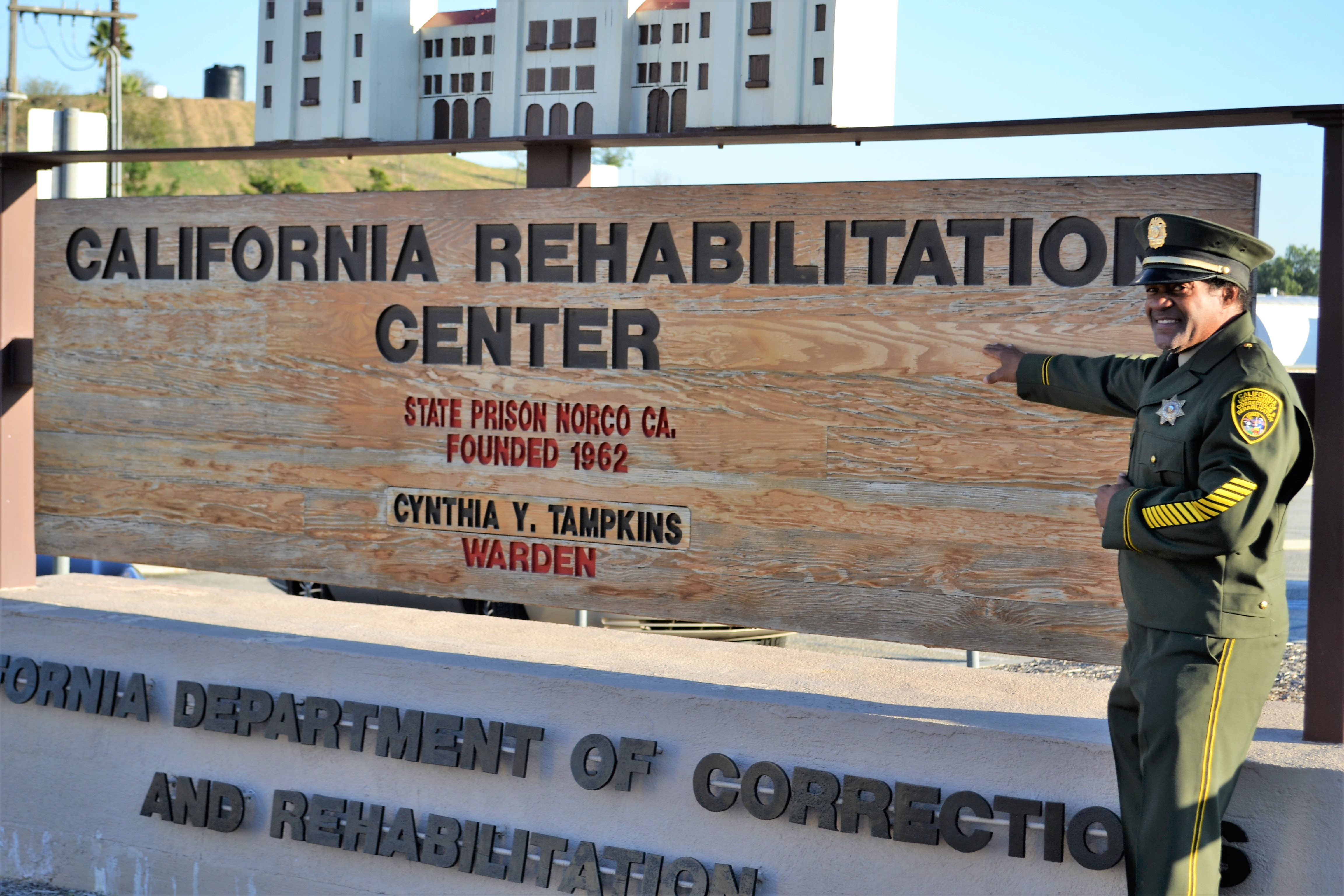 "Man in uniform in front of ""California Rehabilitation Center"" sign."