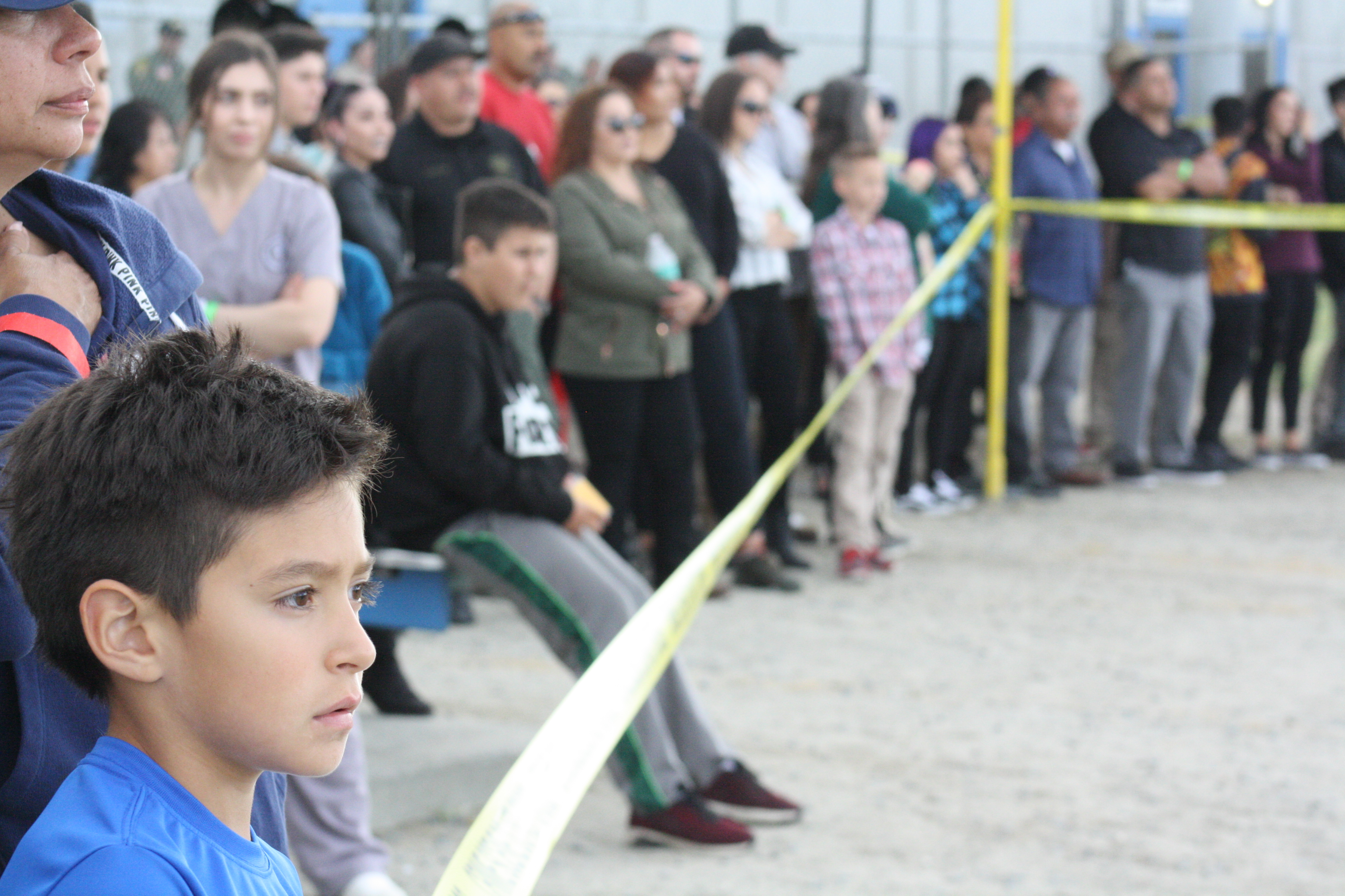 Children and parents look into a roped-off area.