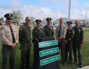 Men in uniform stand behind street signs.