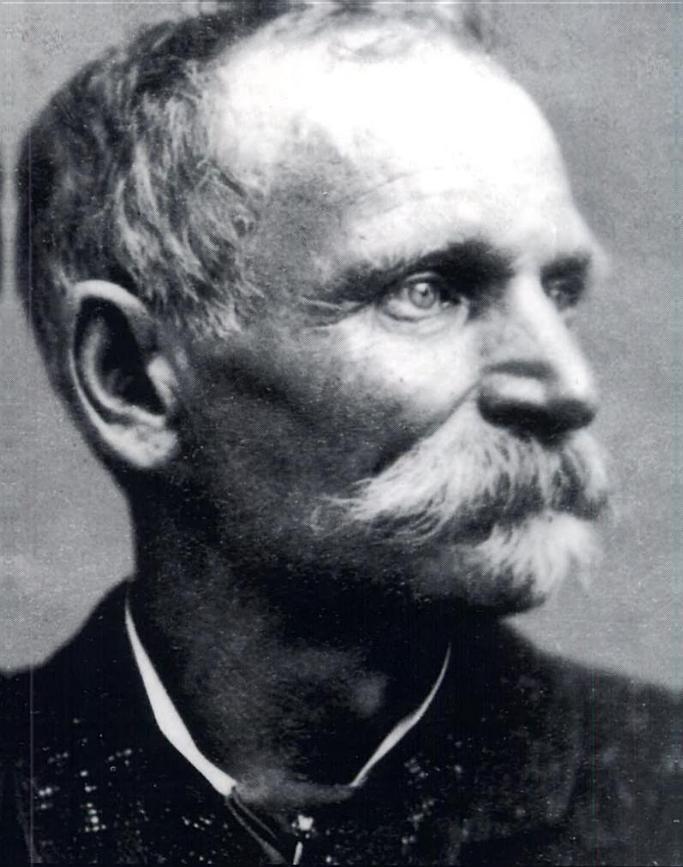 Photo man with mustache, short chin beard and intense eyes.
