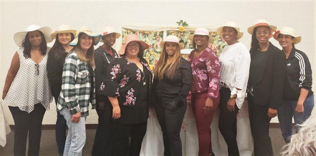 Ten smiling women wear large hats.