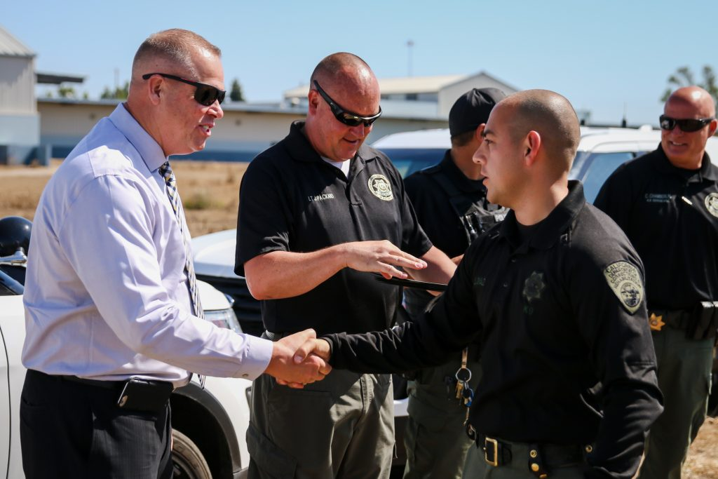 Man in shirt and tie shakes hands with officers.