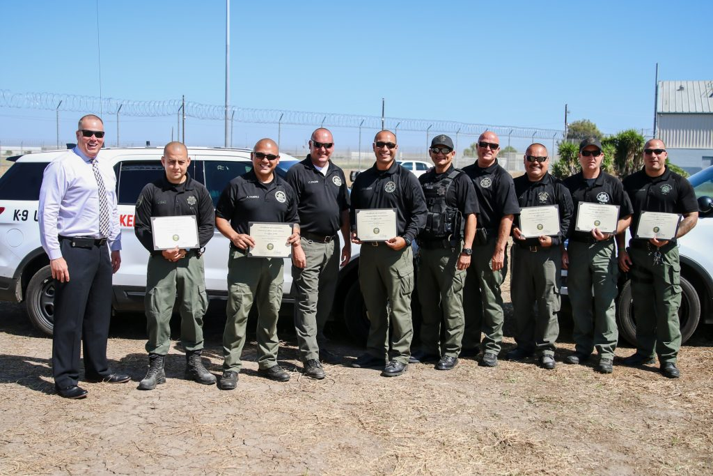 Man in shirt and tie stands beside officers holding certificates.
