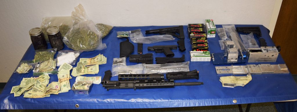 Money, guns, ammunition and drugs are displayed.