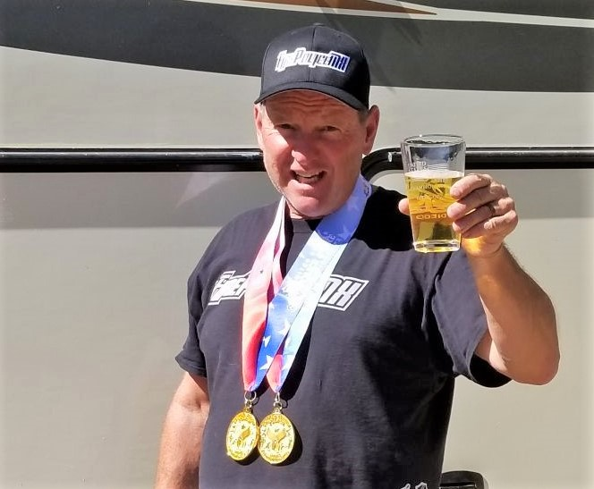 Man toasts with glass while wearing two medals.