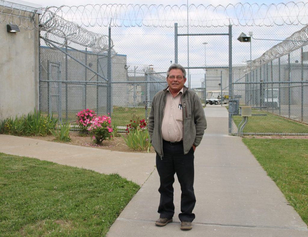 Man stands in front of chain-link fence.