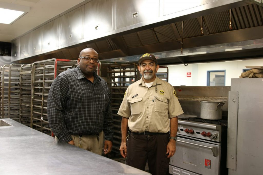Two men stand in prison kitchen.